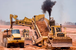 A photograph of a dirt scooper and loader putting dirt into a dumptruck at a construction site.