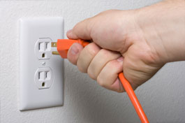 A hand unplugging an electrical appliance from an outlet