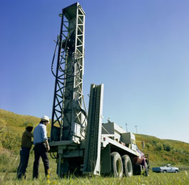 Operators preparing a hole for the explosive charges used in seismic exploration