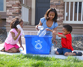 family recycling plastic into bin